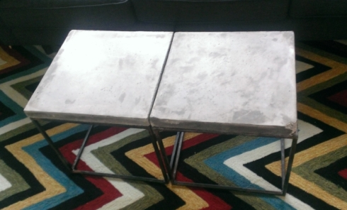 The two concrete-topped tables that form a coffee table. You can see the damaged corner in the lower right.