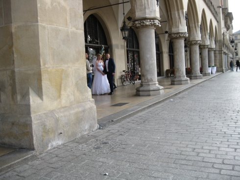 A couple poses in market square for their wedding photographer.