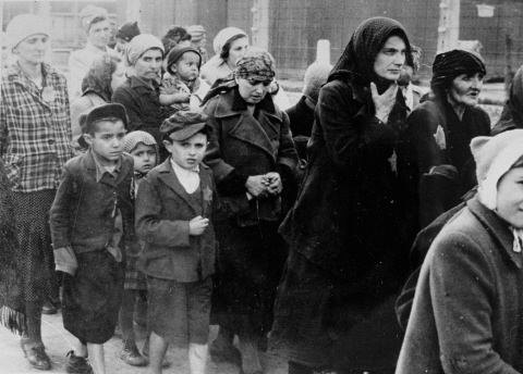 Women and children selected for death, walking unknowingly toward gas chambers, upon arriving at Birkenau.