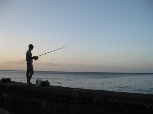 A fisherman casts from the seawall in Havana.