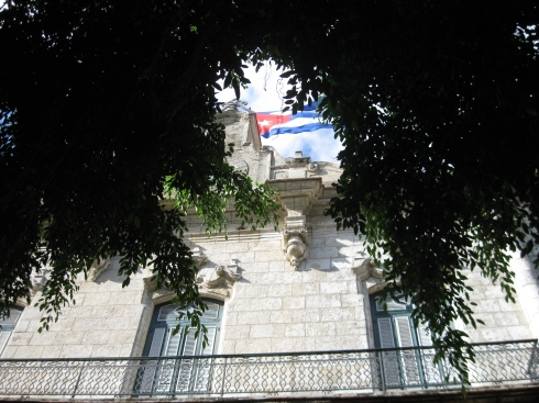 The Cuban flag atop of building on one of Havana's city plazas.