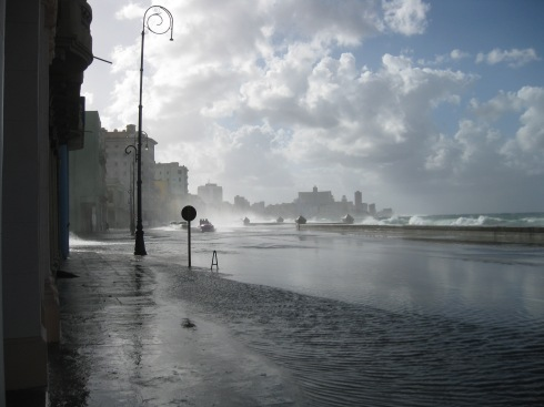 Cars were still driving on the flooded Malecon.